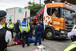 London, UK. 6 September, 2019. Metropolitan Police officers work to remove climate activists who had locked themselves together using an arm tube in one of the two main access roads to ExCel London on the fifth day of a week-long carnival of resistance against DSEI, the world's largest arms fair. The road remained blocked for several hours. The fifth day of protests was themed as Stop The Arms Fair: Stop Climate Change in order to highlight links between the fossil fuel and arms industries.