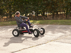 Girl on pedal-operated go-cart