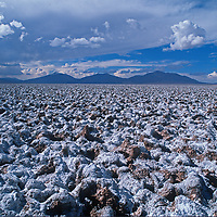 Arid mountains rise behind Salar de Pocitas, a dried lake bed on the vast Altiplano of northern Argentina.