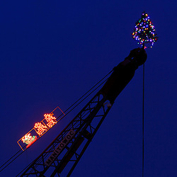 A christmas tree and Santa Claus lights on a crane in Portsmouth, New Hampshire.