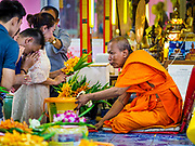"24 JUNE 2017 - BANG KRUAI, NONTHABURI: A Buddhist monk accepts offerings from people before a rebirthing ceremony at Wat Ta Kien (also spelled Wat Tahkian), a Buddhist temple in the suburbs of Bangkok. People go to the temple to participate in a ""Resurrection Ceremony."" Thai Buddhists believe that connecting people by strings around their heads, which are connected to a web of strings suspended from the ceiling, amplifies the power of the prayer. Groups of people meet and pray with the temple's Buddhist monks. Then they lie in coffins, the monks pull a pink sheet over them, symbolizing their ritualistic death. The sheet is then pulled back, and people sit up in the coffin, symbolizing their ritualist rebirth. The ceremony is supposed to expunge bad karma and bad luck from a person's life and also get people used to the idea of the inevitability of death. Most times, one person lays in one coffin, but there is family sized coffin that can accommodate up to six people. The temple has been doing the resurrection ceremonies for about nine years.     PHOTO BY JACK KURTZ"