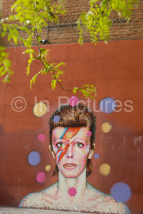 A detail of the mural of iconic musician and singer David Bowie has appeared on the wall of Morleys department store in Brixton, Lambeth, south London. The Bowie face is sourced (by an unknown artist) from the cover of his 1973 album Aladdin Sane at the height of his 1970s fame. The pop icon lived at 40 Stansfield Road, Brixton, from his birth in 1947 until 1953. This cover appeared in Rolling Stone's list of the 500 greatest albums of all time, making #277.