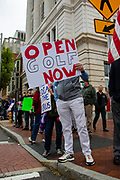 """A man holds a sign reading """"open golf now"""" at the ReOpen PA Rally in Harrisburg, Pennsylvania on April 20, 2020. Protesters gathered at the Pennsylvania Capitol to demand that Governor Tom Wolf reopen the state's economy. (Photo by Paul Weaver)"""