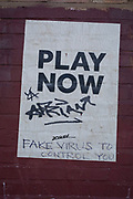 Fake virus to control you graffiti on a poster which reads Play Now in central Birmingham under the Coronavirus outbreak on 31st March 2020 in Birmingham, England, United Kingdom. Following government advice most people are staying at home leaving the streets quiet, empty and eerie. Coronavirus or Covid-19 is a new respiratory illness that has not previously been seen in humans. While much or Europe has been placed into lockdown, the UK government has announced more stringent rules as part of their long term strategy, and in particular social distancing.