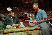 """Matthieu and Abdul Rashid Khan (father was Afghan Haji) inside his yurt wearing the Kyrgyz hat called Kalpak. Kara Jelgha (""""black valley"""") summer camp. The campment of Abdul Rashid Khan, the """"king"""" of the Kyrgyz, who took over after the famed Rahman Qul seeked refuge in Pakistan and then Turkey.<br /> <br /> <br /> Adventure through the Afghan Pamir mountains, among the Afghan Kyrgyz and into Pakistan's Karakoram mountains. July/August 2005. Afghanistan / Pakistan."""