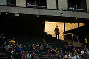 A fan walks through the carousel in a patch a light before the Oakland Athletics host the Baltimore Orioles at Oakland Coliseum in Oakland, Calif. on August 8, 2016. (Stan Olszewski/Special to S.F. Examiner)