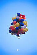 John Ninomiya, a cluster balloonist rises to 4500 feet above the San Joaquin valley near Coalinga.  Cutting Balloons away to descend and dumping water from water containers by his side to rise Ninomiya can control his altitute and to an extent, his direction of travel.
