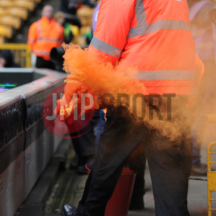 Stewards deal with a smoke canister at Molineux Stadium - Photo mandatory by-line: Paul Knight/JMP - Mobile: 07966 386802 - 02/05/2015 - SPORT - Football - Wolverhampton - Molineux Stadium - Wolverhampton Wanderers v Millwall - Sky Bet Championship