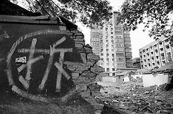 """Sign on wall saying """"demolish"""" modern apartments to rear in Beijing"""