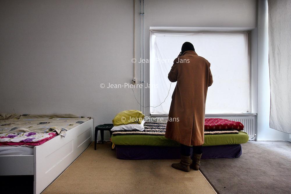 """Nederland, Amsterdam , 23 december 2014.<br /> Gekraakt opvangtehuis voor """"gedumpte"""" Marokkaanse vrouwen.<br /> Op de foto: 1 van de vrouwen mobiel aan het bellen in 1 van de gekraakte ruimtes in het opvangtehuis.<br /> Foto:Jean-Pierre Jans"""