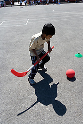 Boy playing hockey in school playground,