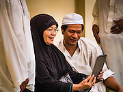 06 JULY 2016 - BANGKOK, THAILAND: A family looks at pictures on their iPad before Eid services at Ton Son Mosque in the Thonburi section of Bangkok. Eid al-Fitr is also called Feast of Breaking the Fast, the Sugar Feast, Bayram (Bajram), the Sweet Festival or Hari Raya Puasa and the Lesser Eid. It is an important Muslim religious holiday that marks the end of Ramadan, the Islamic holy month of fasting. Muslims are not allowed to fast on Eid. The holiday celebrates the conclusion of the 29 or 30 days of dawn-to-sunset fasting Muslims do during the month of Ramadan. Islam is the second largest religion in Thailand. Government sources say about 5% of Thais are Muslim, many in the Muslim community say the number is closer to 10%.        PHOTO BY JACK KURTZ