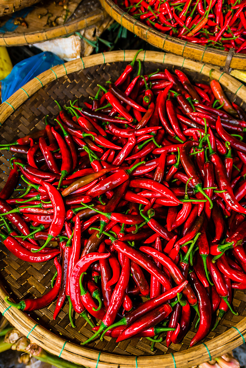 Red and green chiles and other produce at a street market in Hue, Central Vietnam.