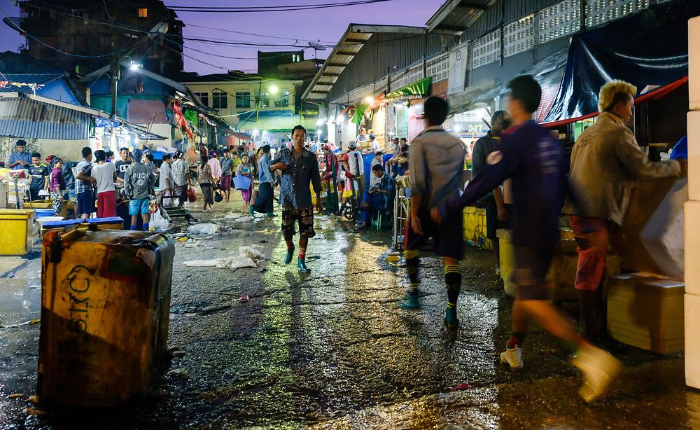 YANGON, MYANMAR - People walking at Yangon fish market at dawn.