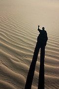 Man's shadow on sand dunes in Death Valley National Park, California
