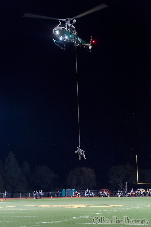 A Sheriffs deputy is air lifted out of the stadium after delivering the game ball as the Del Oro Golden Eagles varsity football team host the Oak Ridge Trojans, Friday Oct 21, 2016.<br /> photo by Brian Baer