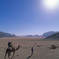 A Bedouin boy leads a traveler on a camel ride in Jordan's Wadi Rum, part of the Arabian Desert.