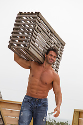 rugged sexy man carrying a lobster trap