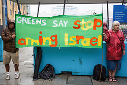 London, UK. 14th September, 2021. Green Party activists hold a banner at a Stop The Arms Fair protest outside the entrance to ExCeL London on the first day of the DSEI 2021 arms fair. Activists from a range of different groups have been protesting outside the venue for one of the world's largest arms fairs for over a week.