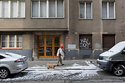 A local lady takes her little dogs out for a cold walk along Kostelni street, Holesovice district, Prague 7, on 18th March, 2018, in Prague, the Czech Republic.