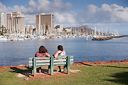 Two women on a bench at Ala Moana Beach Park look towards Waikiki.