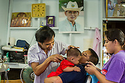 13 JANUARY 2013 - BANGKOK, THAILAND:  A woman comforts her son while he gets his first haircut in the Bang Luang neighborhood in Bangkok. The Bang Luang neighborhood lines Khlong (Canal) Bang Luang in the Thonburi section of Bangkok on the west side of Chao Phraya River. It was established in the late 18th Century by King Taksin the Great after the Burmese sacked the Siamese capital of Ayutthaya. The neighborhood, like most of Thonburi, is relatively undeveloped and still criss crossed by the canals which once made Bangkok famous. It's now a popular day trip from central Bangkok and offers a glimpse into what the city used to be like.     PHOTO BY JACK KURTZ