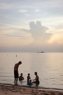 Srithanu, Ko Phangan, Thailand - June 30, 2017: Adults and children enjoy the sea at sunset on Zen Beach.