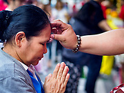 19 OCTOBER 2018 - BANGKOK, THAILAND: A woman is annointed during Navratri celebrations in Bangkok. Navratri is a nine night (10 day) long Hindu celebration that marks the end of the monsoon and honors of the divine feminine Devi (Durga). The festival is celebrated differently in different parts of India, but the common theme is the battle and victory of Good over Evil based on a regionally famous epic or legend such as the Ramayana or the Devi Mahatmya. Navratri is celebrated throughout Southeast Asia in communities that have a large Hindu population.  PHOTO BY JACK KURTZ