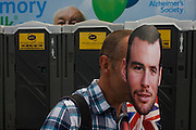 With a charity billboard behind, a spectator wears a mask with the face of Team GB road cycling hero Mark Cavendish on the first day of competition of the London 2012 Olympic 250km mens' road race. Starting from central London and passing the capital's famous landmarks before heading out into rural England to the gruelling Box Hill in the county of Surrey. Local southwest Londoners lined the route hoping for British favourite Cavendish to win Team GB first medal but were eventually disappointed when Kazakhstan's Alexandre Vinokourov eventually won gold.
