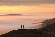 Walkers enjoy a spectacular sunset from Mam Tor, Peak District