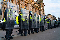 Glasgow, Scotland, UK. 15 May 202. Rangers football supporters  celebrating 55th league victory are cleared from George Square by police in riot gear on Saturday evening. In very violent scenes police were pelted with bottles and items from a nearby construction site as police pushed the supporters into the south west corner of the square. Pic; Police in riot gear await orders to enter George Square.  Iain Masterton/Alamy Live News.