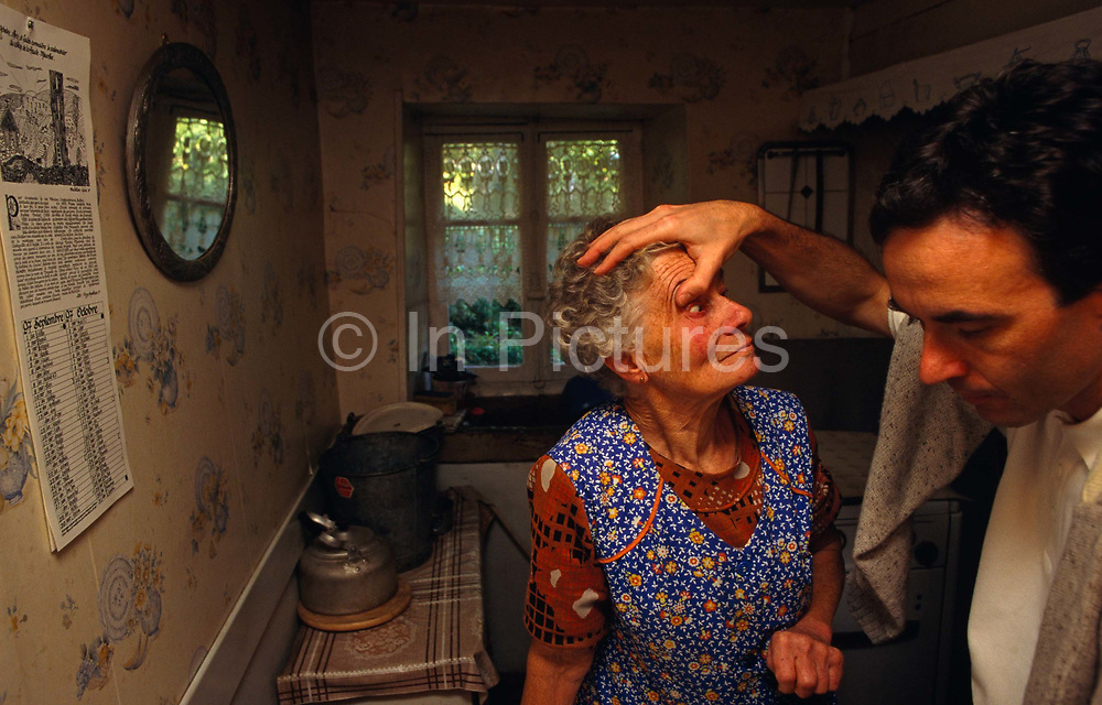 In the privacy of her own country home, an elderly French lady is about to have eye-drops administered by her local doctor in the Vosges town of Ban de Laveline. Holding her eyelids up with a thumb in preparation of giving the woman the necessary medicine, the young health professional reaches for his equipment and the lady is left looking rather startled and uncomfortable for a few moments as her eye stares wildly. We are in her small cottage on the outskirts of town and the doctor is making his rounds to various patients unable to attend his daily surgery. The lady wears a colourful apron, typical of French working people, and is possibly in her seventies, living alone with only kind neighbours to ensure her safety. <br /> <br /> <br /> <br /> http://www.france-voyage.com/en/