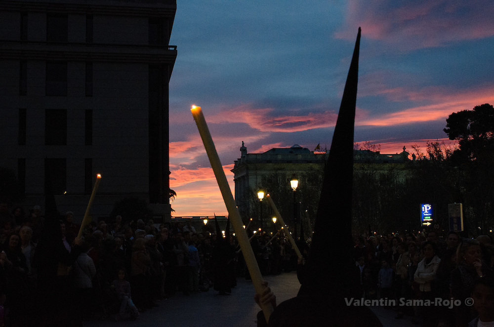 'Nazareno' carrying a large candle during sunset at Plaza de Oriente square in Madrid during Palm Sunday procession.