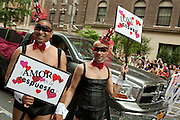 """A couple in costume in the 2011 Pride Parade 1n New York's West Village. They bear signs in Spanish and English, """"Amor es la respuesta"""" and """"Love is the anser."""""""