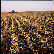 Farm equipment working in a farm field of corn stalk stubble.