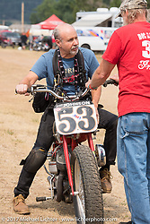 Michael Lichter tries out Brent Johnson's tank shift brakeless Indian Scout racer during the Spirit of Sturgis Vintage Motorcycle Races at the Sturgis half mile track during the annual Sturgis Black Hills Motorcycle Rally. Sturgis, SD. USA. Saturday August 5, 2017. Photography ©2017 Michael Lichter.