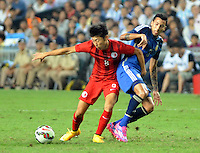 Santiago Vergini of Argentina, right, challenges Xu Deshuai of Hong Kong during a friendly football match in Hong Kong, China, 14 October 2014.<br /> <br /> Lionel Messi needed just six minutes to make his mark in Argentina's 7-0 rout of Hong Kong in a friendly at Hong Kong Stadium on Tuesday (14 October 2014). The Barcelona star Messi scored twice after going on as a substitute for the last 30 minutes of the game to celebrate the 100th anniversary of the Hong Kong Football Association. Napoli striker Gonzalo Higuain and Benfica's Nicolas Gaitan also scored two goals each after Sevilla's Ever Banega had opened scoring in the 19th minute.