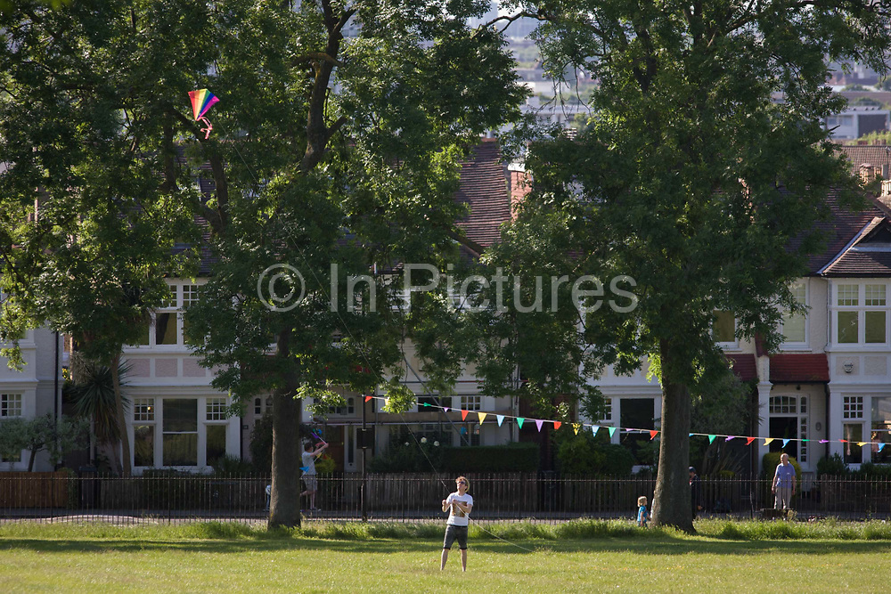 Man flies kite on a summer evening in front of Edwardian period homes in Ruskin Park, south London. Lambeth council have allowed the blocking off of this small residential street and house owners are erecting the bunting that stretches across the road in advance of a street party in which neighbours bring out tables and food for all to enjoy. The Kite flyer is inside the park that borders the street with just enough of a breeze to maintain flight.