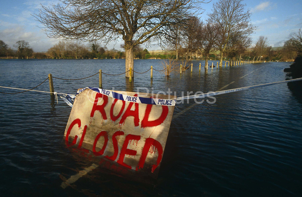 Police tape and a makeshift sign warn of a lane closure due to flooding in the village of Lavant, West Sussex. Afternoon sunshine illuminates the roughly-made board with red painted letters which says 'Road Closed'. The rippling water is less than a foot deep and we can see the broken white centre line beneath the surface but the linked posts that border the village green are also submerged. Even so, traffic is prohibited from passing through there for the risk of grounding or damaging engines. Lavant is a village just north of the city of Chichester. It is made up of two parts, Mid Lavant and East Lavant, and takes its name from the River Lavant which flows from East Dean. This area has been prone to flooding for several years and houses around the rising rivers can be blighted with insurance companies refusing future cover.