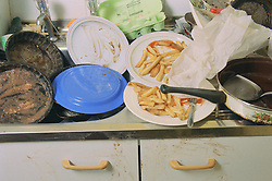 Kitchen sink in house full of dirty plates and pans,
