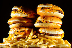 File photo dated 09/07/14 of a pile of cheeseburgers and french fries. New rules banning junk food advertising across all children's media - including online and social - are coming into effect as part of efforts to tackle childhood obesity.