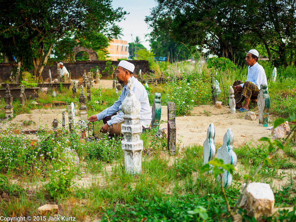 19 JUNE 2015 - PATTANI, PATTANI, THAILAND: Men pray next to graves in the Muslim cemetery in Pattani. Perkuboran To'Ayah is the Muslim cemetery in Pattani. It is more than 150 years old. The last Sultan of Pattani, who ruled until Siam (Thailand) annexed Pattani is buried in the cemetery. Many victims of political and sectarian violence that has wracked Thailand's three Muslim majority provinces, Pattani, Narathiwat and Yala are also buried in the cemetery. On Fridays, after morning prayers, Muslim men come to the cemetery to tend to the graves of their family members.   PHOTO BY JACK KURTZ