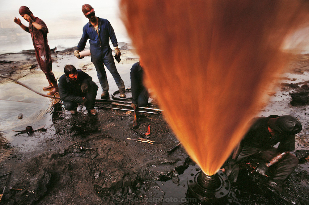 An oil well fire specialist of Red Adair, Co. of Texas works to prepare a well for capping by sawing off the damaged well head in the Kuwait oil fields. The fire has already been extinguished but the well is spewing oil and gas into the air under high pressure. The trick is to cut through the metal casing cleanly without causing any sparks that could reignite the well and incinerate the workers. The company was one of those brought in to fight the Kuwait oil well fires after the end of the Gulf War (July, 1991) More than 700 wells were set ablaze by retreating Iraqi troops creating the largest man-made environmental disaster in history.