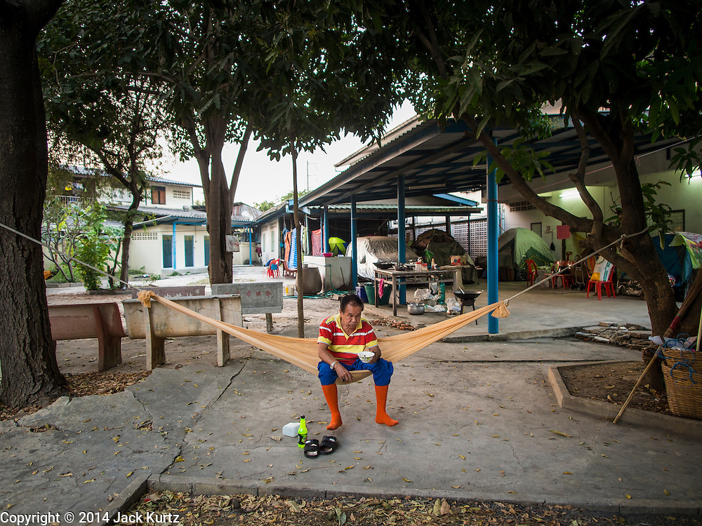"""25 JANUARY 2014 - BANG LUANG, NAKHON PATHOM, THAILAND: A performer with the Sing Tong Teochew opera troupe relaxes in a hammock before a show in a Chinese shrine in the town of Bang Luang, Nakhon Pathom, Thailand. The Sing Tong Teochew opera troupe has been together for 60 years and travels through central Thailand and Bangkok performing for mostly ethnic Chinese audiences. Chinese opera was once very popular in Thailand, where it is called """"Ngiew."""" It is usually performed in the Teochew language. Millions of Chinese emigrated to Thailand (then Siam) in the 18th and 19th centuries and brought their cultural practices with them. Recently the popularity of ngiew has faded as people turn to performances of opera on DVD or movies. There are still as many 30 Chinese opera troupes left in Bangkok and its environs. They are especially busy during Chinese New Year when travel from Chinese temple to Chinese temple performing on stages they put up in streets near the temple, sometimes sleeping on hammocks they sling under their stage.     PHOTO BY JACK KURTZ"""
