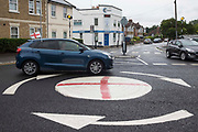 A vehicle flying a small England flag passes a mini-roundabout painted with the St George's flag on 10th July 2021 in Windsor, United Kingdom. The Royal Borough of Windsor and Maidenhead repainted several roundabouts for safety reasons previously daubed with England flags before England's Euro 2020 quarter-final match against Ukraine but it appears that local residents have restored them in advance of the Euro 2020 final between England and Italy.