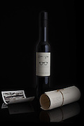 A styled photograph of Grove and Vine's first olive oil release. The client wanted to show the black and white image taken of the region and also the typewritten tasting notes rolled in a scroll. Such a beautiful bottle and presentation to emphasize on a black background and surface