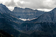 View of Bird Woman Falls (center bottom) and the snow field that feeds it as seen from Going to the Sun Road in Glacier National Park, Montana, Tuesday, October 7, 2014. The cirque above the falls used to contain a small glacier but no longer has one.
