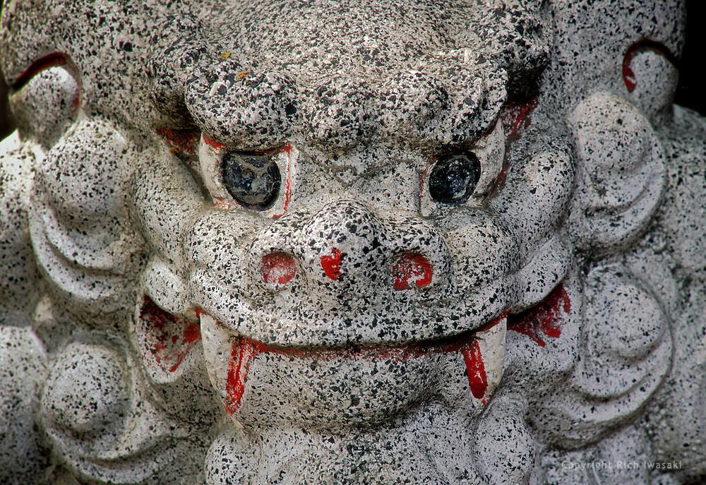 Closeup view of stone guardian lion near entrance to local shrine in Misawa, Aomori Prefecture, Japan