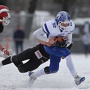 Darien quarterback Silas Wyper is sacked by Cole Harris, New Canaan, during the New Canaan Rams Vs Darien Blue Wave, CIAC Football Championship Class L Final at Boyle Stadium, Stamford. The New Canaan Rams won the match in snowy conditions 44-12. Stamford,  Connecticut, USA. 14th December 2013. Photo Tim Clayton