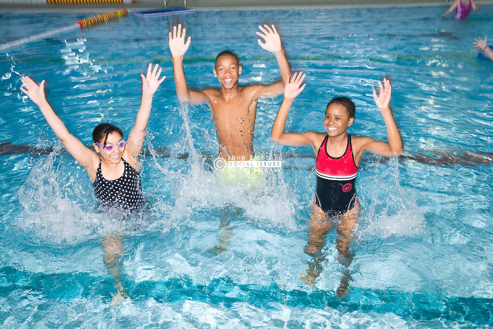 Group of children splashing around in the swimming pool at their local leisure centre,